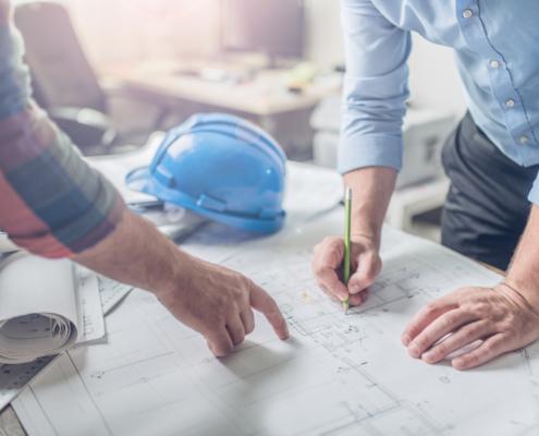 Hände und Baupläne bei der Arbeit